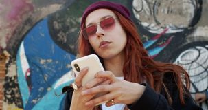 Close up of the young pretty woman in hipster style, with red hair, in sunglasses and hat typing and texting a message. Close up of the young pretty Caucasian stock video