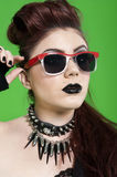 Close-up of young punk woman wearing sunglasses over green background Royalty Free Stock Image