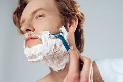 Close up. Young red haired guy neatly shaves royalty free stock image