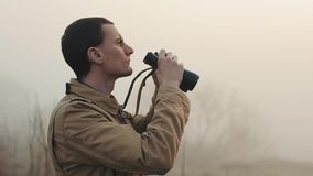 Close up of Young redhead man in khaki coat holding a binoculars looking sunrise and sunset on background. Fog around. Close up of Young redhead man in khaki stock footage