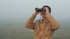 Close up of Young redhead man in khaki coat holding a binoculars looking sunrise and sunset on background. Fog around. Close up of Young redhead man in khaki stock video