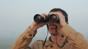 Close up of Young redhead man in khaki coat holding a binoculars looking sunrise and sunset on background. Fog around. Close up of Young redhead man in khaki stock video footage