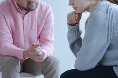 Close-up of a young sad woman sharing her grief with a psychotherapy specialist during an individual counseling meeting. Close-up of a young sad women sharing stock images