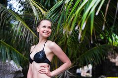 Close-up of young sexy slim girl standing on a beach wearing black bikini swimwear with green palm leaf on the. Background. She is tanned and stylish Royalty Free Stock Images