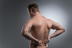 Close-up of young shirtless man with back pain. Royalty Free Stock Photos