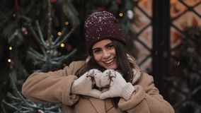 Close Up of Young Smiling Beautiful Girl in Winter Clothes Standing in Falling Snowflakes Outside, Looking, Making Heart stock video