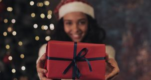 Close up of young smiling mulatto girl in santas hat gives and takes back the red present box with blue ribbon to camera. Standing at Christmas tree lighting at stock video footage
