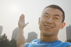 Close up of young, smiling, muscular man stretching, hands outstretched in Beijing, China Royalty Free Stock Image