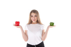 A close up of young and smiling woman who is holding red and green bell peppers. Healthy diet and vitamins. Vegetarian food. Royalty Free Stock Photo