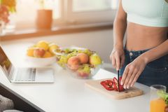 Close up. A young sports girl is standing in the kitchen and is preparing a salad. It has a blue topic. Stock Photos