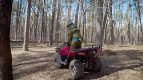Close up of a young sportsman operating pink ATV standing on it and moving through forest trail. Young explorer is. Close up of a young sportsman dressed in stock footage