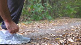 Close up of young sportsman ties shoe in early autumn forest. Athlete tying shoelaces on sneakers before jogging during. Training outdoor. Feet of strong man stock video