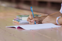 Close up of  young student hands writing on notebook Stock Images