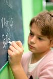 Close up of young student writing on chalkboard. Close up of young student writing with chalk on chalkboard in classroom Stock Photos
