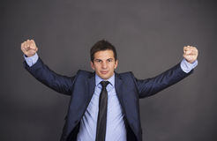 Close-up of a young successful businessman laughing with arms ra Royalty Free Stock Photography