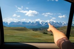 Close-up of a young tourist showing his finger. The direction of traffic for a further adventure on top of a mountain in car covered with snow against a blue royalty free stock image