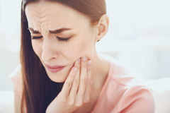 Close up of young unhappy woman which having toothache. Need a dentist. Pretty unhappy woman closing her eyes and touching her jowl while having toothache royalty free stock photos