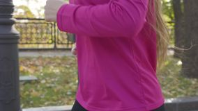Close-up of a young unrecognizable Caucasian girl with long tail hair wearing sportswear running in the autumn park. Female runner training in the morning stock footage