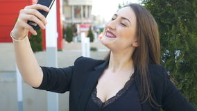 Close-up of young urban business woman taking selfie with smartphone in the city. Closeup of young urban business woman taking selfie with smartphone in the city stock video footage