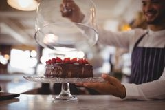 Close up of young waiter holding glass lid over cake on cakestand at counter stock photo