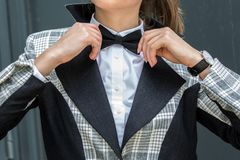 Close up of young Woman Adjusting her black bow tie in white shi. Rt and black and gray jacket and a black bow tie Stock Images