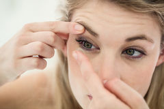 Close-up of young woman applying contact lens Stock Images
