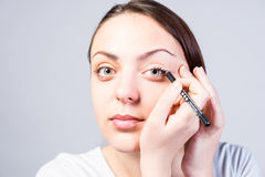 Close up Young Woman Applying Eyeliner Makeup. Close up Smiling Young Woman Applying Eyeliner Makeup to Left Eye While Looking at the Camera on a Gray Background stock images