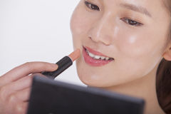 Close up of young woman applying lipstick in a mirror, studio shot Royalty Free Stock Photography