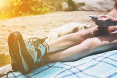Close up of young woman bare legs with hiking boots. Holding and using cell phone with dog nearby over plaid blanket outdoors with golden glow from the sun Royalty Free Stock Photos
