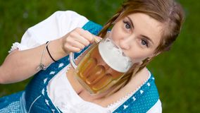 Blonde oktoberfest girl drinks beer and laughs