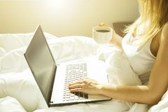Big spacey hotel room full of sunlight and sun beams. Optimistic start of the day. Blond woman cozy home clothing welcoming the mo stock photos