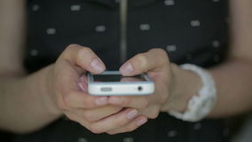 Close up of young woman black dress fingers typing on her smartphone.  stock footage