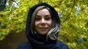 Close up young woman in black jacket with a hood on autumn nature background. Portrait young woman in black jacket with a hood on autumn nature background. Close stock footage