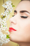 Close up of young woman and blossomed tree branch Stock Images