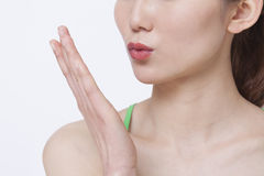 Close up of young woman blowing a kiss, studio shot Stock Photos
