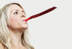 Close-up of a young woman blowing party blower against gray background Royalty Free Stock Photo
