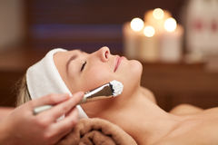 Close up of young woman and cosmetologist in spa Royalty Free Stock Images