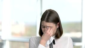 Close up young woman is crying. Portrait of crying woman wiping the tears in her eyes over blurred background stock video