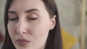 Close up young woman disguises makeup rosacea on face stock footage