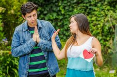 Close up of young woman with a disgusting face holding in her hands a letter, with a worried boyfriend looking the girl. Close up of young women with a Royalty Free Stock Image