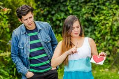Close up of young woman with a disgusting face holding in her hands a letter, with a worried boyfriend looking his. Close up of young women with a disgusting Stock Photography
