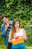 Close up of young woman doing a face of detesting the gift she is holding in her hands, with thoughtful boyfriend behind. Close up of young women doing a face of Stock Photography