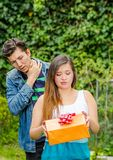 Close up of young woman doing a face of detesting the gift she is holding in her hands, with thoughtful boyfriend behind. Close up of young women doing a face of Royalty Free Stock Photography