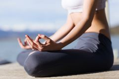 Close-up of young woman doing yoga next to the lake. Close-up of fit and sporty young woman doing yoga next to the lake Royalty Free Stock Image