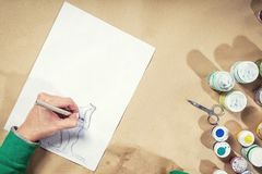Close-up of a young woman  draws. Close-up of a young woman in a green sweater draws her left hand with a pencil on a white sheet on a wooden table, on which Stock Photography