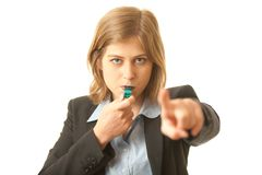 Female Whistle Blower Pointing at You. Close up of a young woman dressed in a business suit. She is blowing a whistle and pointing at you. Concept for whistle Royalty Free Stock Photo