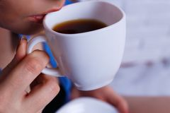 Close up of young woman drinking coffee from fine white cup. Coz Royalty Free Stock Images