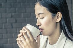 Close up young woman drinking relaxing coffee. In coffee shop Royalty Free Stock Photos