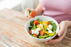 Close up of young woman eating salad at home Stock Photos