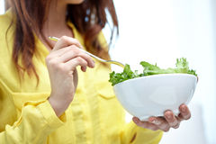 Close up of young woman eating salad at home Royalty Free Stock Images